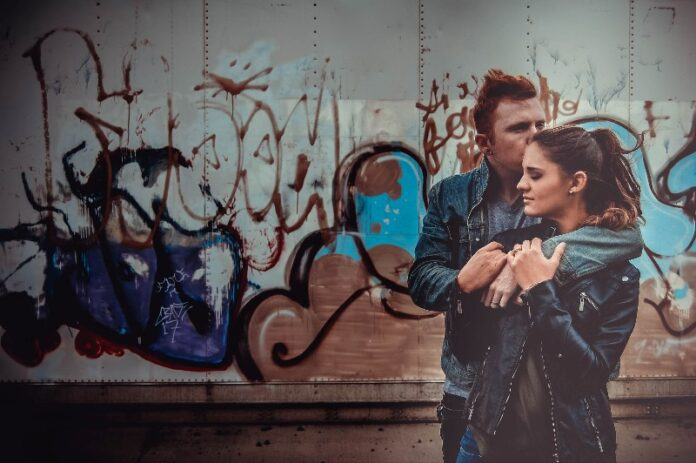 Couple hugging in front of graffiti wall