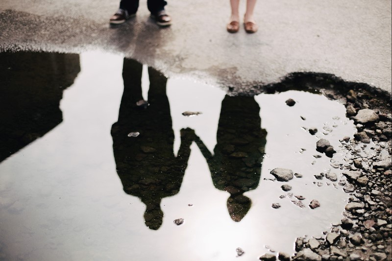Reflection in a puddle of couple holding hands