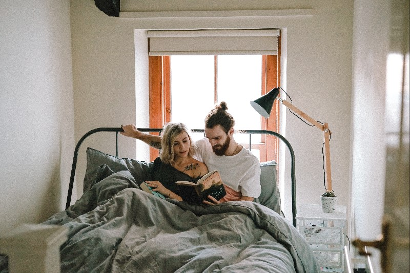 Couple Sitting in bed reading a book