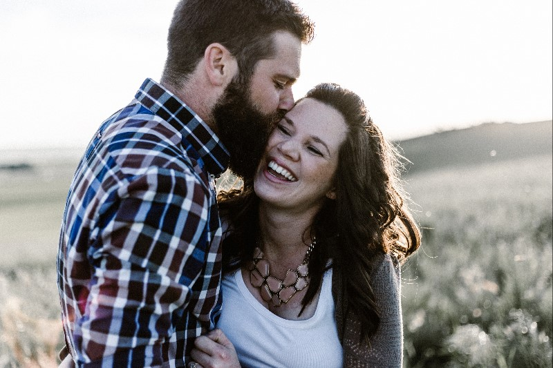 Couple in country side, man kissing woman's cheek