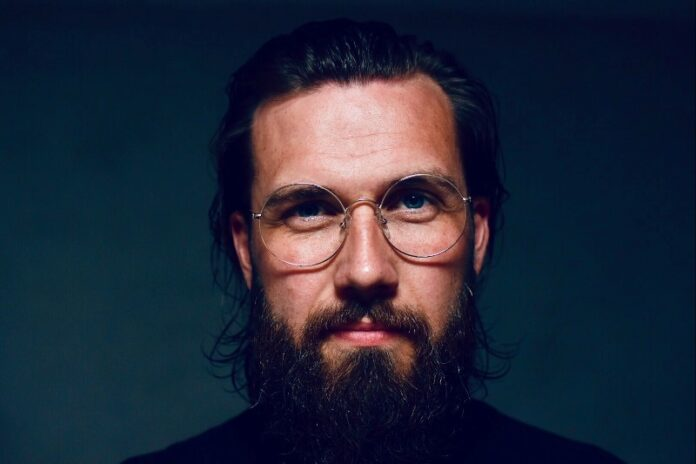 Man with Beard wearing glasses with green background
