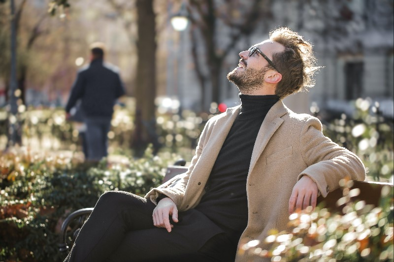 Man sitting on park bench smiling at sky