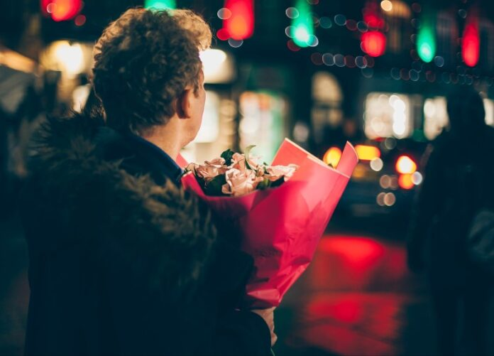 Man holding bunch of flowers, city lights in the back ground