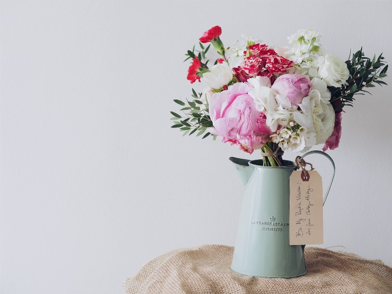pink and white Flowers in vase on wooden table