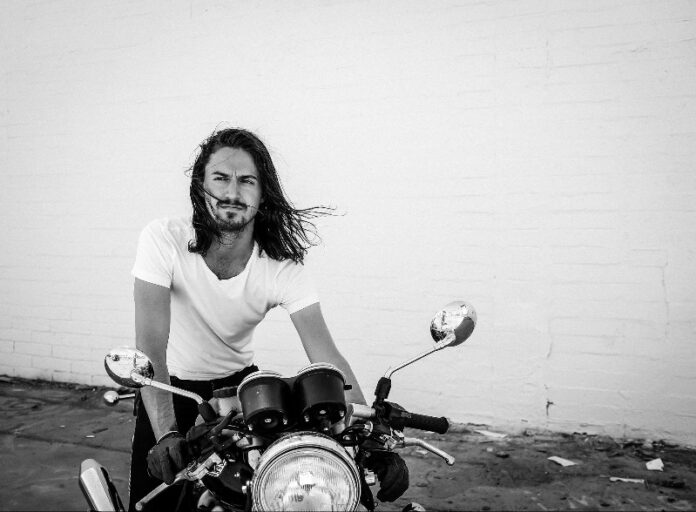 Man with beard and long hair sitting on bike black and white photo