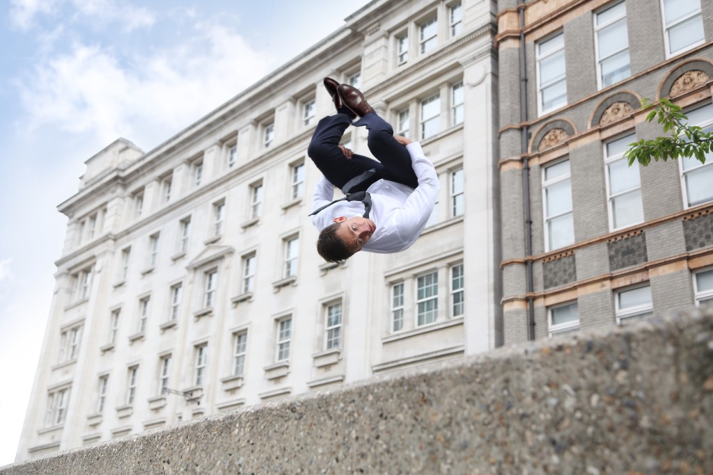 man jumping across building in a suit