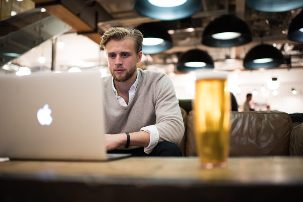 man working remotely on computer with a pint of beer