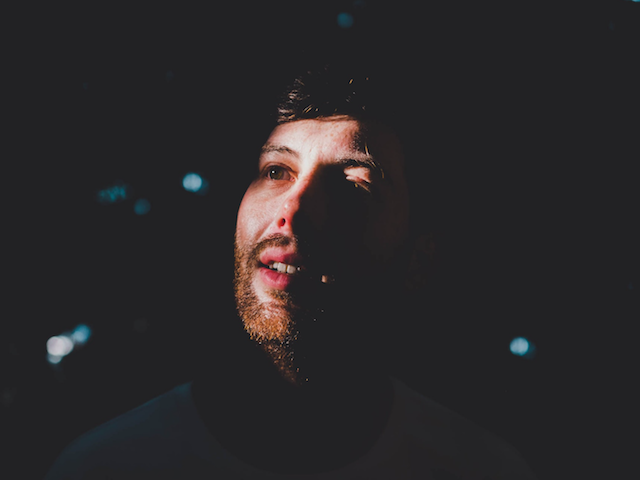 man looking into sky in dark room