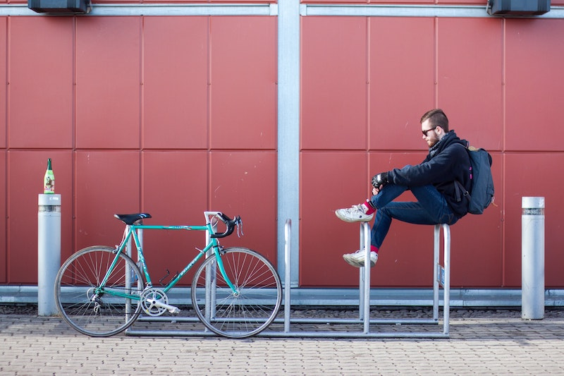 man sitting on bike rack with tapered jeans