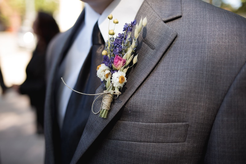 close up of groom with flowers in suit