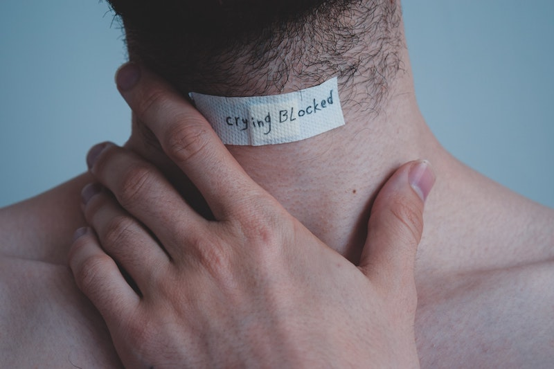 Crying blocked written on bandaid across mans neck
