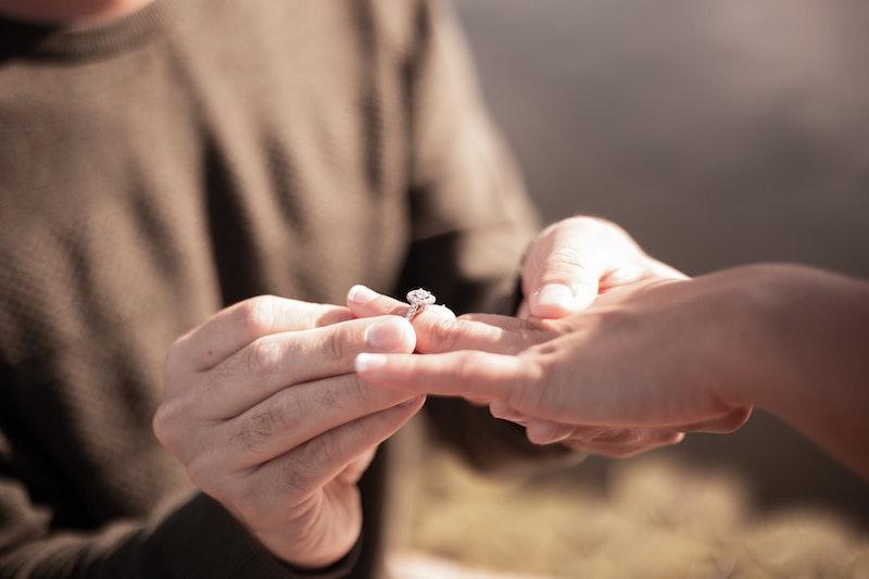 Man putting ring on womens finger