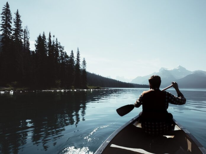 Man paddling boat in lake with mountains in the distance