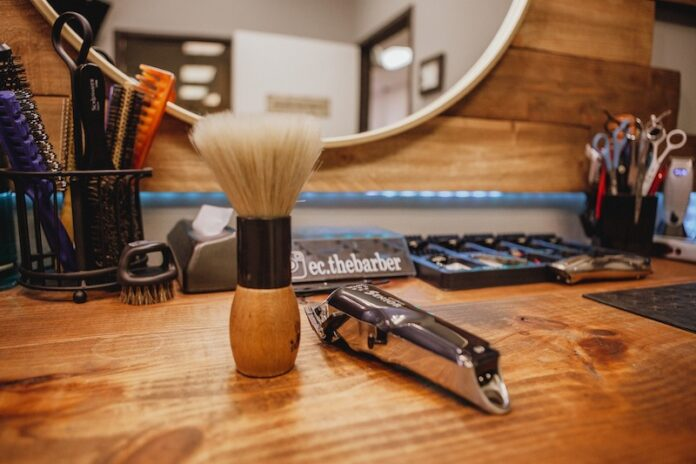 Shaving cream brush and shaver on wooden work bench with mirror in the background