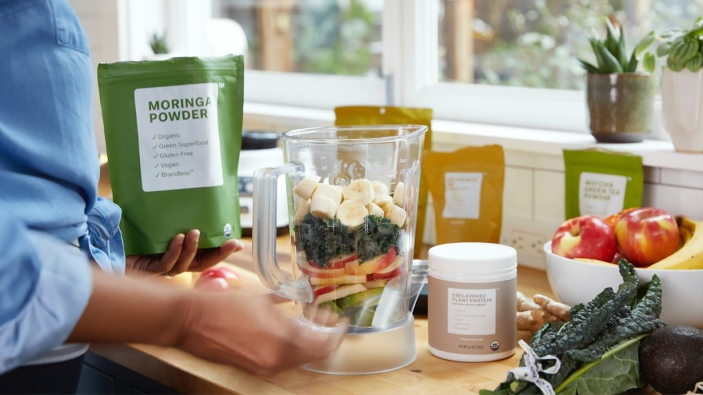 probiotics and supplements going into a blender full of fruit.