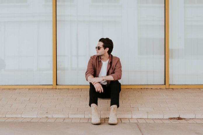 Man sitting on concrete bench looking to the left