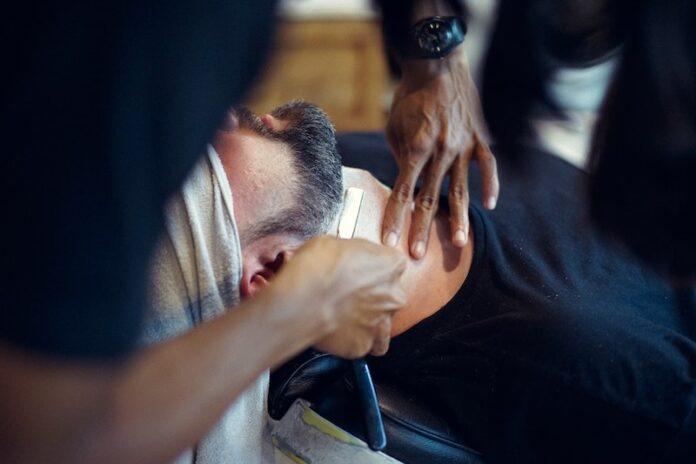 Barber using straight razor to trim beard