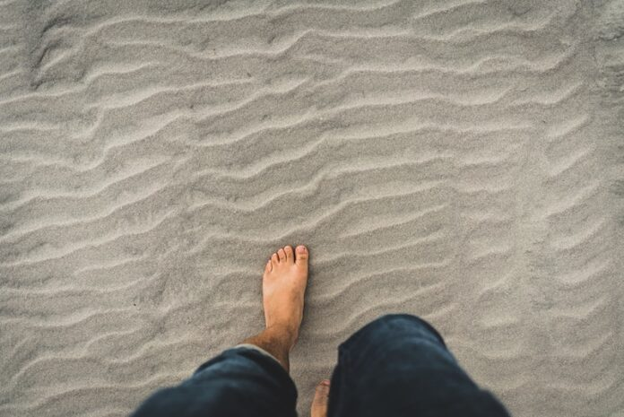 Man's feet walking on rippled sand