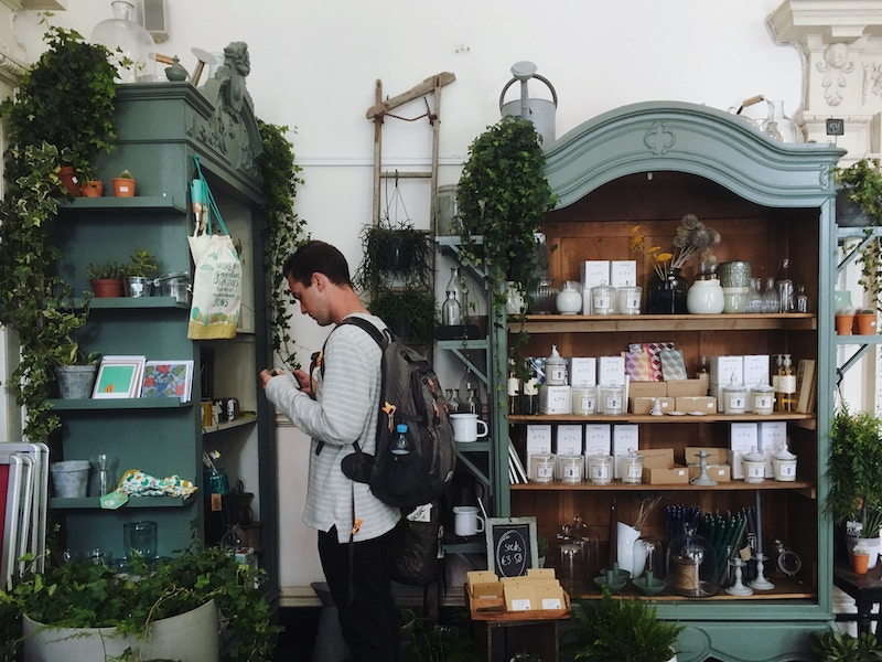 man with backpack looking at items in a shop