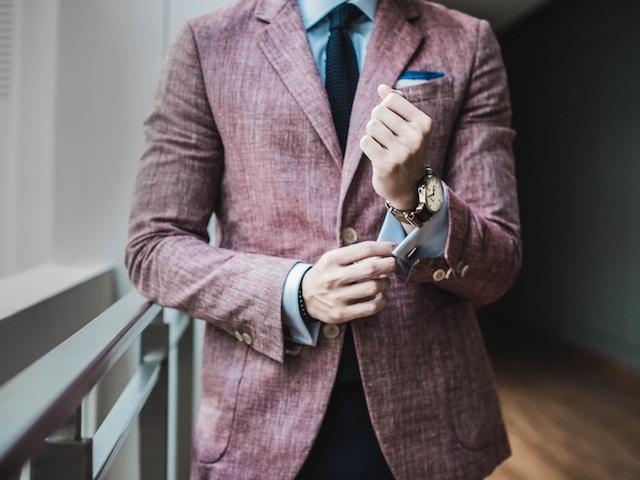man in suit adjusting cuffs