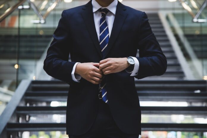Man in suit doing up jacket button