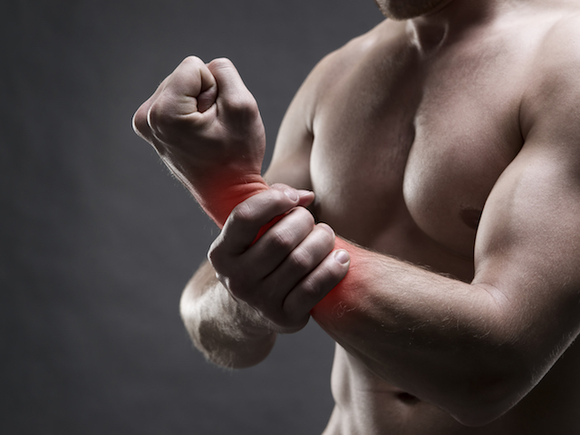 Pain in the hand. Muscular male body. Handsome bodybuilder posing on gray background with red dot