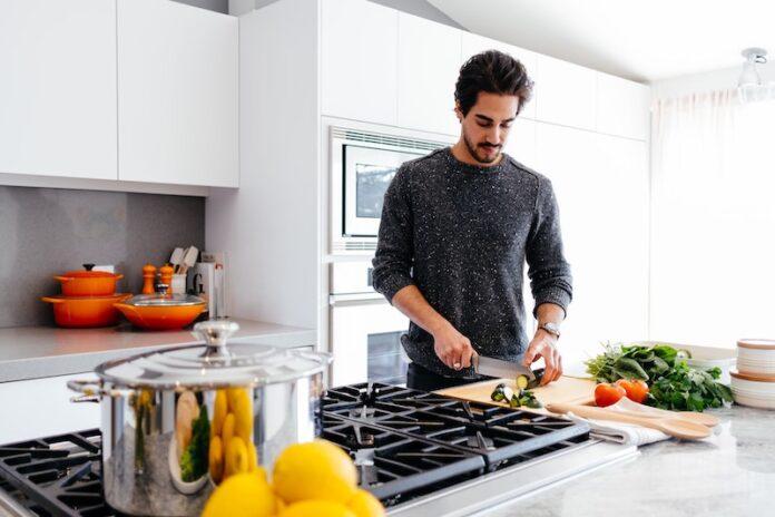 Man in kitchen cutting food
