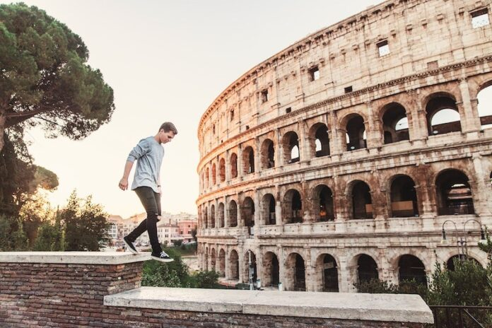 Man walking on ledge in front of the colloseum in Rome