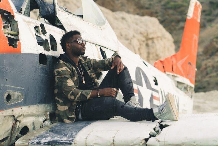 Cargo jacket on man sitting on wing of plane