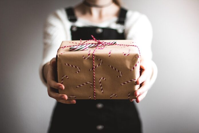 Person passing present wrapped in Christmas paper