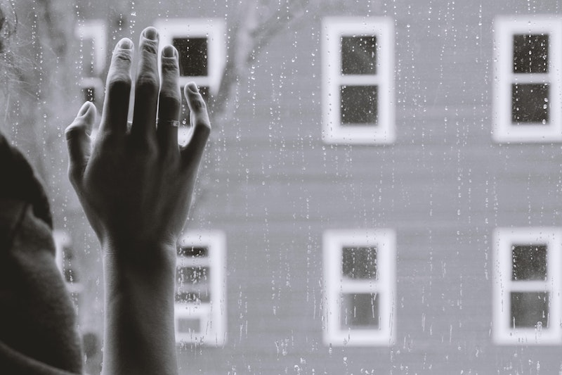 hand against rainy window