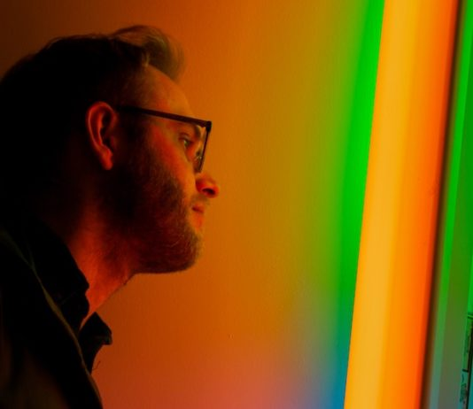 bearded man standing in front of color light