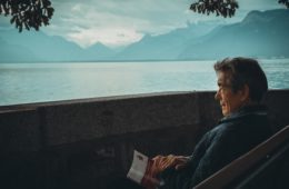 man reading travel book with mountains and river in background