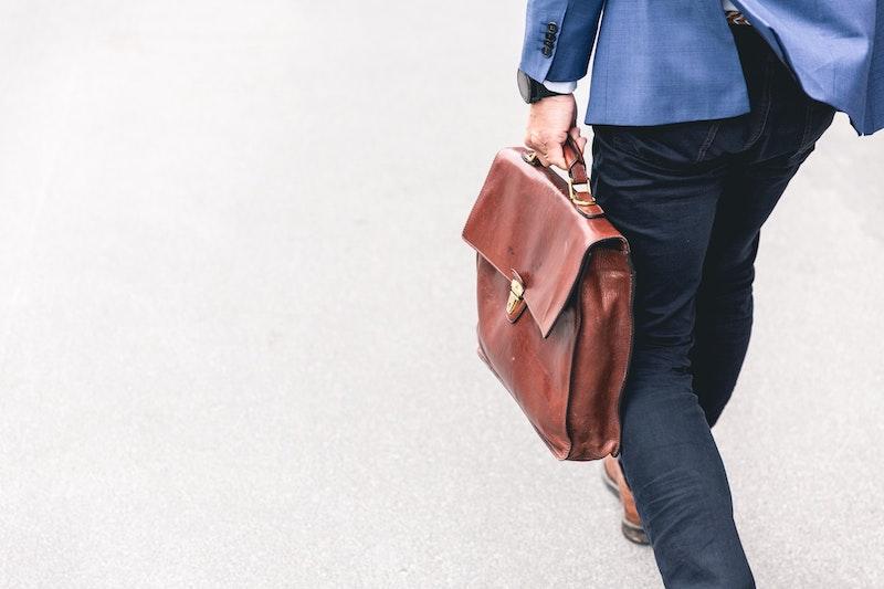 Man walking holding brown leather bag