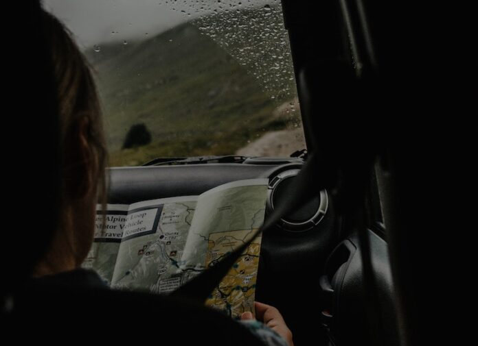 Looking over shoulder of passenger in car looking at a map