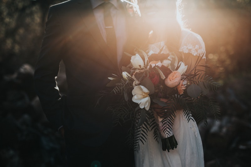 Married couple together with flowers and sun in the background
