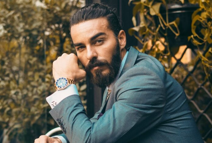 Man leaning on table with watch and man bun