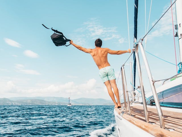 man hanging off side of boat