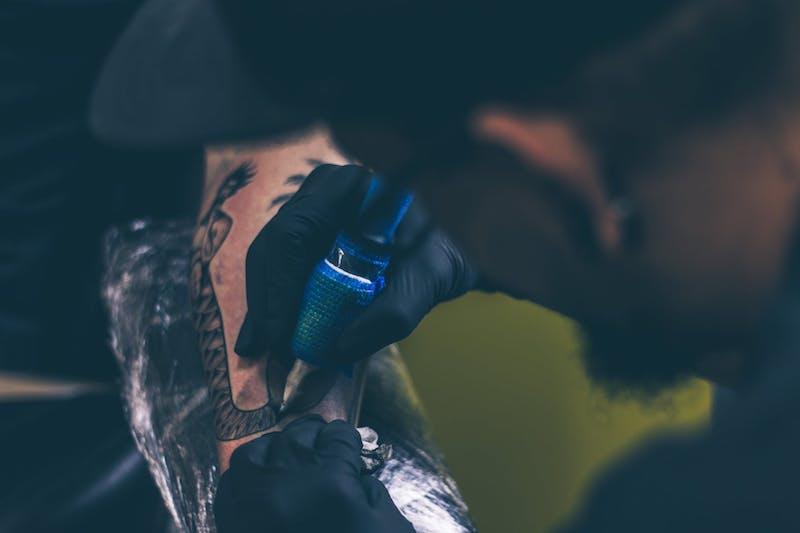 tattoo artist tattooing arm