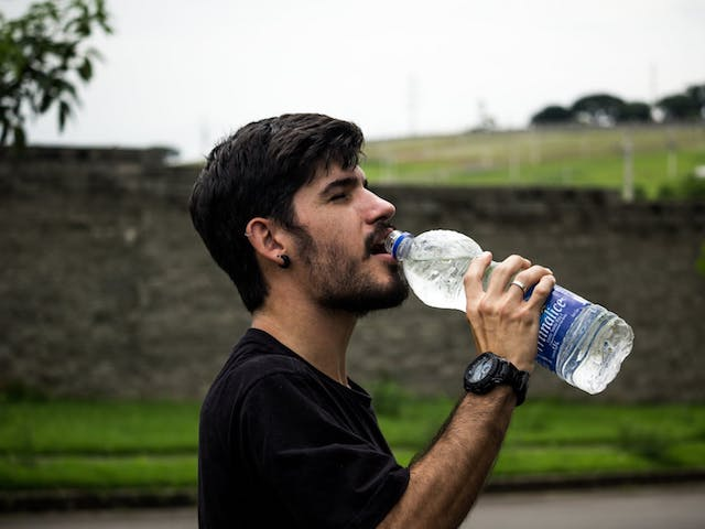 man drinking bottle of mineral water