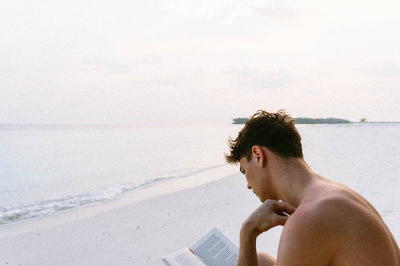 man reading book on beach