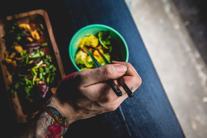 hand eating from bowl of healthy food