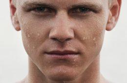 mans face with water splashing