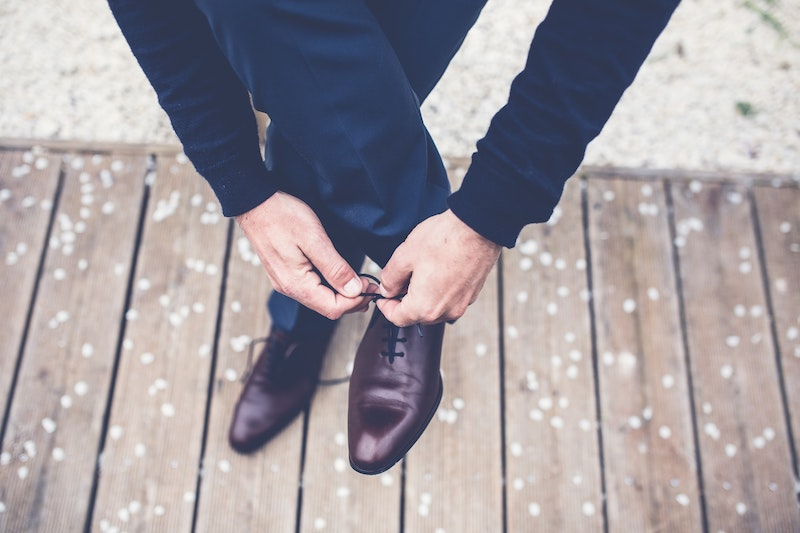 man bending over to tie shoes