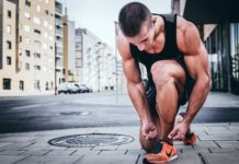 muscular man tying shoe laces