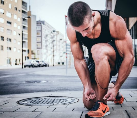 muscular man tying shoe laces