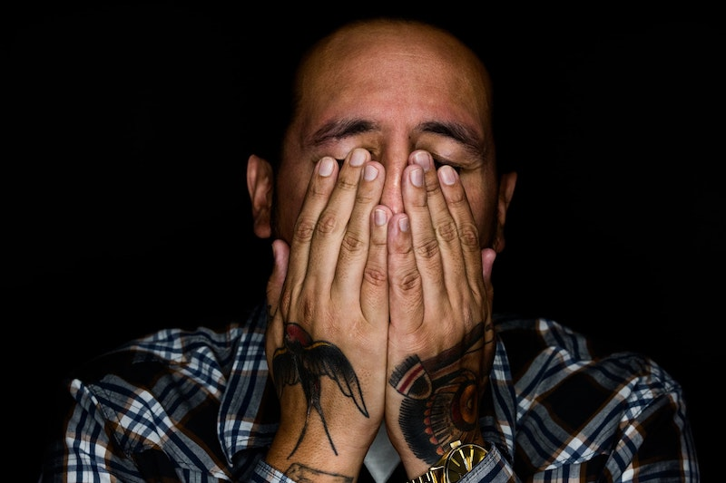 man stressed with hands over face