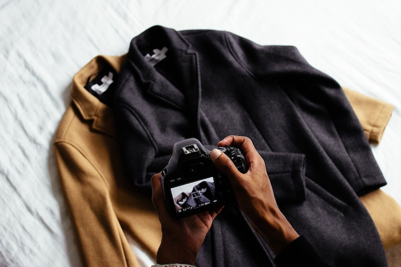 person taking photos of coats