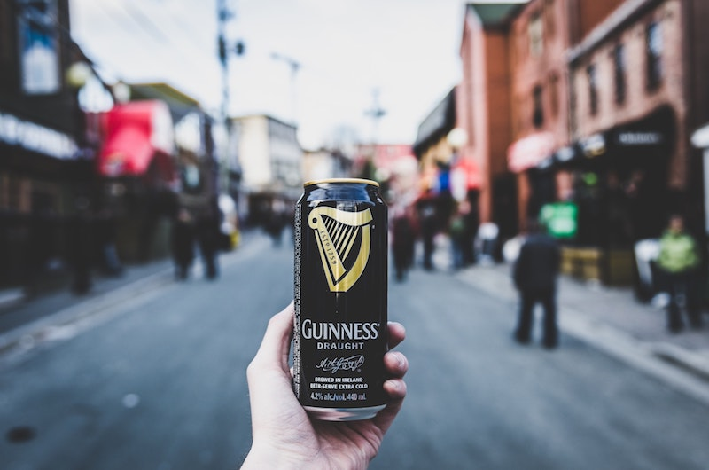 man holding can of guinness