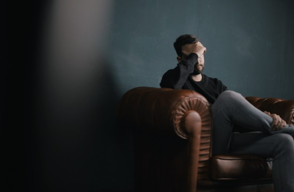 man with mens hormonal imbalance sitting on a chair